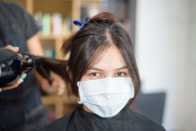A young woman is getting a haircut in a hair salon , wearing face mask for protection covid-19 , salon safety concept Premium Photo