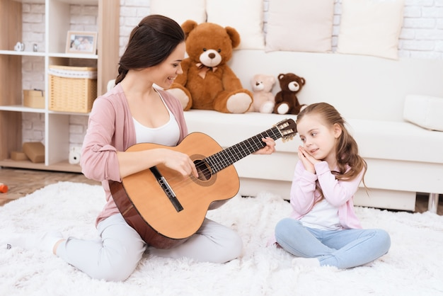A young woman is playing guitar, and a girl is singing. Premium Photo