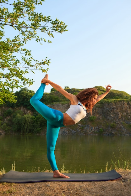 若い女性は川の近くのヨガを練習しています。 無料写真