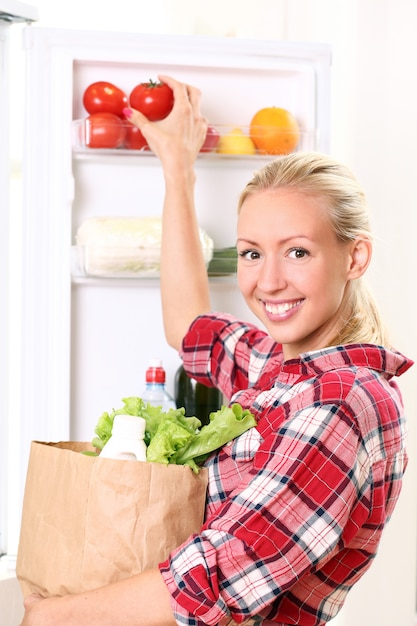 Young woman is putting a food into the fridge Free Photo