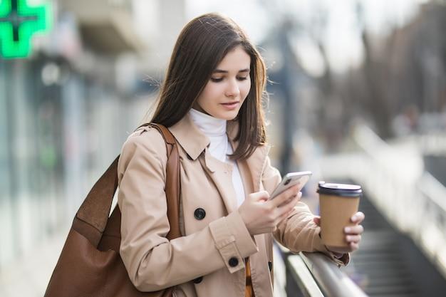 Молодая женщина читает новости на свой телефон за пределами Бесплатные Фотографии