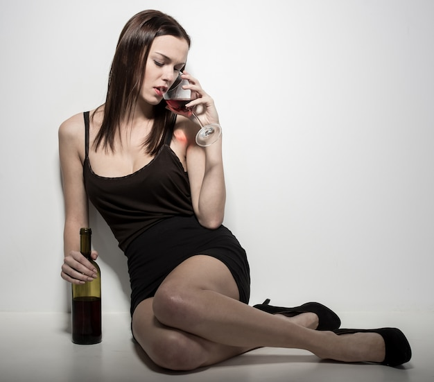 A young woman is sitting on the floor with a glass of wine. Premium Photo