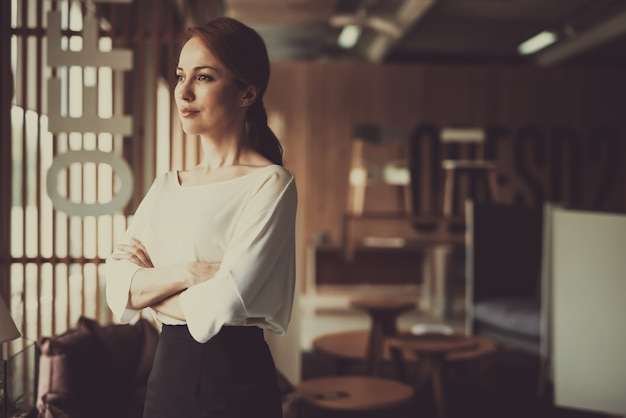 Young woman is standing in office arms akimbo Premium Photo