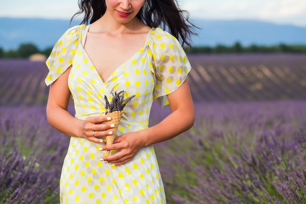 Young woman is standing with lavender flowers in a waffle cup holding in a hand. Premium Photo