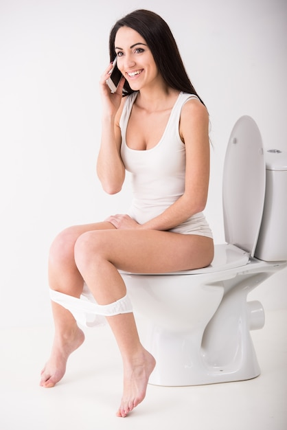 Young woman is talking by phone while seated on toilet. Premium Photo
