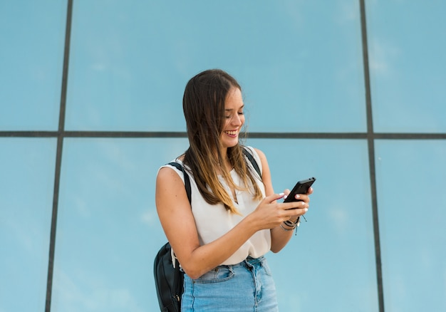 Young woman is using her smartphone, there is a mirror behind her Premium Photo