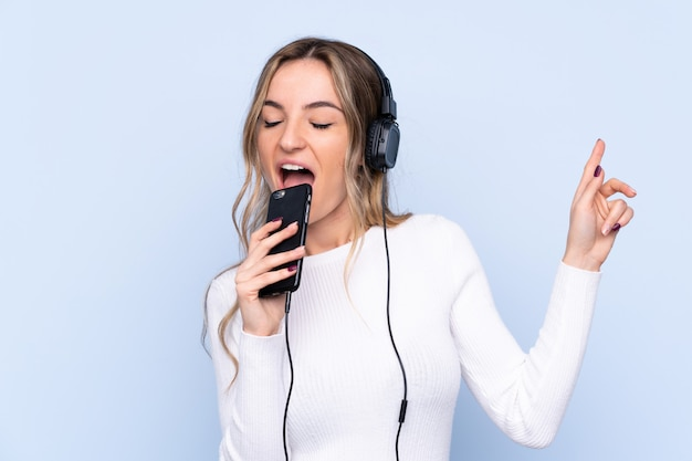 Young woman over isolated blue wall listening music with a mobile and singing Premium Photo