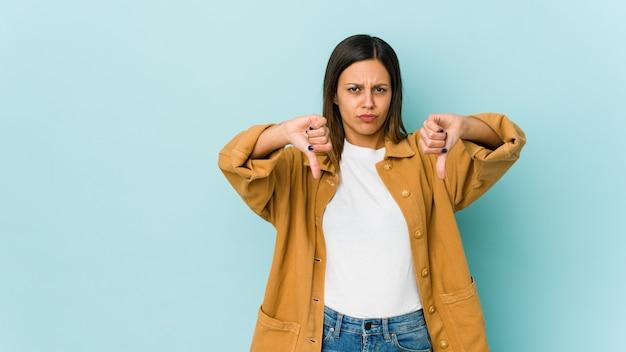 Молодая женщина изолирована на синем, показывая большой палец вниз и выражая неприязнь. Premium Фотографии