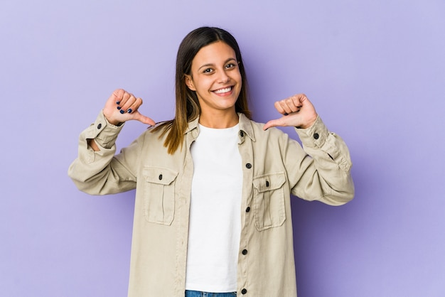 Young woman isolated on purple wall feels proud and self confident, example to follow. Premium Photo