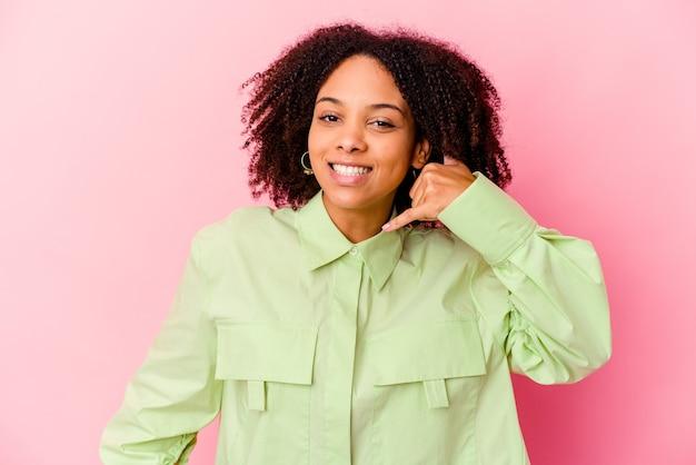 손가락으로 휴대 전화 제스처를 보여주는 고립 된 젊은 여자 프리미엄 사진