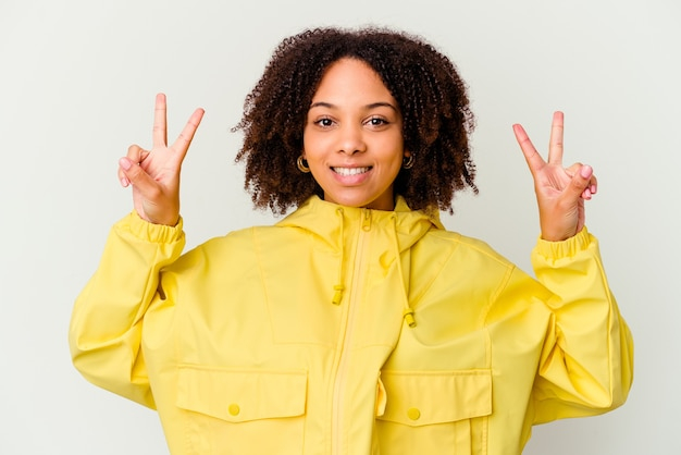 若い女性は、勝利のサインを示して、広く笑って孤立 Premium写真