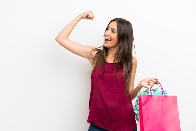 Young woman over isolated white wall holding a lot of shopping bags Premium Photo