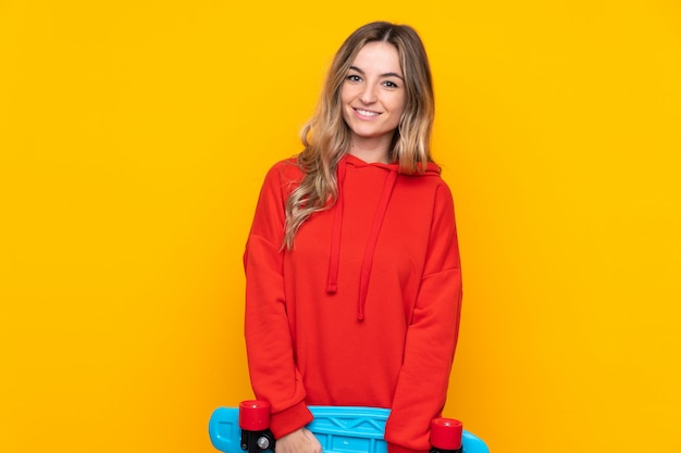 Young woman over isolated yellow wall with a skate with happy expression Premium Photo