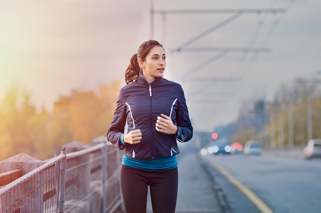 早朝に路上でジョギングする若い女性 Premium写真