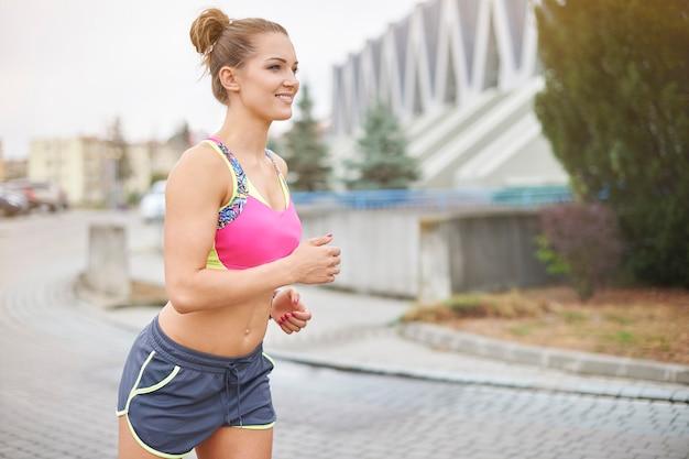 ジョギングや屋外で走っている若い女性。市はジョギングに行く多くの機会を与えます 無料写真