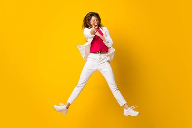 Young woman jumping over isolated yellow wall pointing to the front Premium Photo