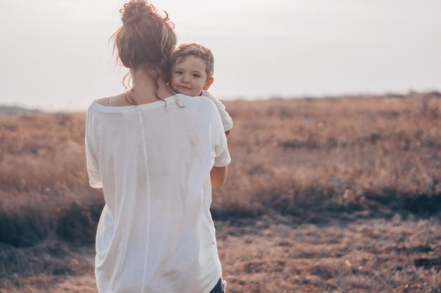 Молодая женщина целует своего маленького сына на солнце на лугу на закате. молодая мать держит своего ребенка. мать и маленький сын, хорошо проводящие время на природе. Premium Фотографии