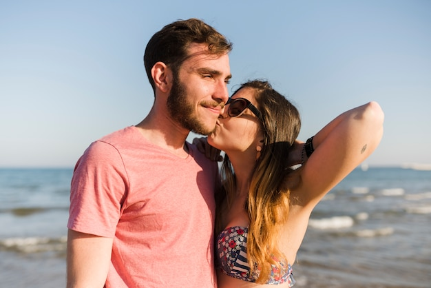 Young woman kissing her boyfriend at beach Free Photo