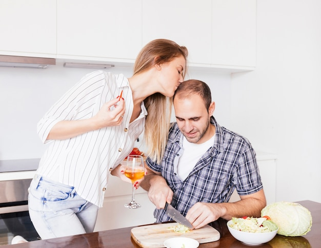 Young woman kissing her husband's forehead cutting the cabbage with knife Free Photo