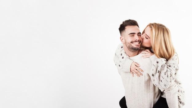 Young woman kissing man in cheek Free Photo