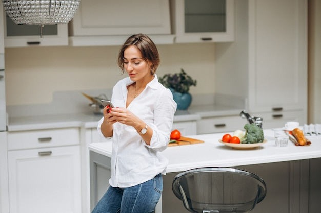 Young woman at kitchen cooking breakfast and talking on the phone Free Photo