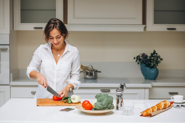 Young woman at kitchen cooking breakfast Free Photo