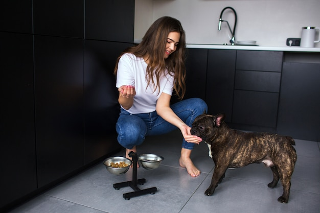 Young woman in kitchen during quarantine. girl sit in squat pose and feed french bulldog. adult pet eating dog food. pet care. Premium Photo