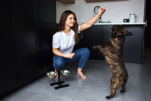 Young woman in kitchen during quarantine. girl traning french bulldog using dog food and playing with pet. darkskinned dog jump up. Premium Photo
