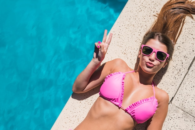 Young woman laying by pool and showing peace gesture Free Photo