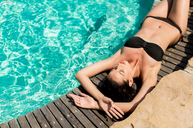 Young woman laying by the pool Premium Photo