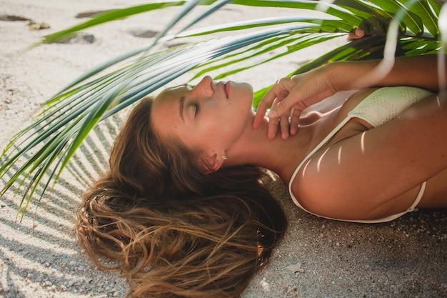 Молодая женщина, лежа на песчаном пляже под пальмовым листом Бесплатные Фотографии