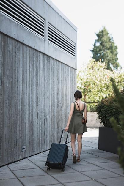 スーツケースをリードする若い女性 無料写真