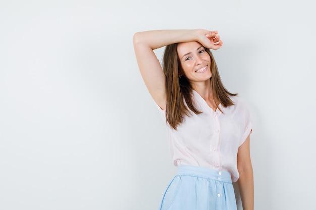 Giovane donna pendente braccio alzato sulla testa in t-shirt, gonna e che sembra felice. vista frontale. Foto Gratuite