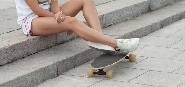 スケートパークでスケートボードの若い女性の足 Premium写真