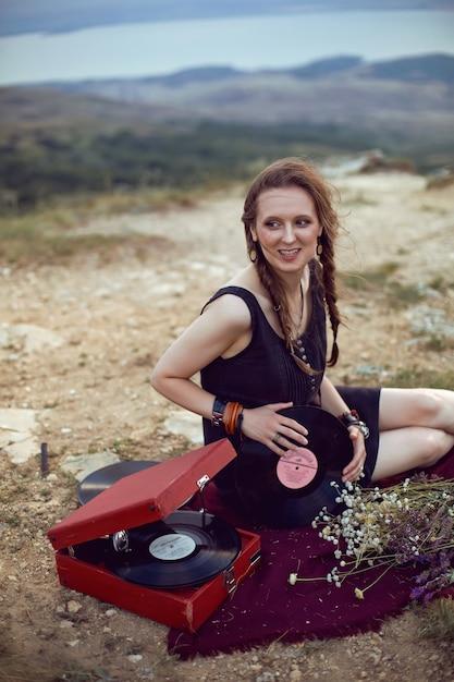 Молодая женщина лежит на природе в черном платье рядом со старым граммофоном и слушает музыку Premium Фотографии