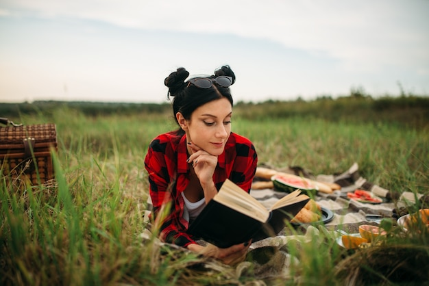 Young woman lies on plaid and reads book, picnic in summer field. romantic junket, happy holiday Premium Photo