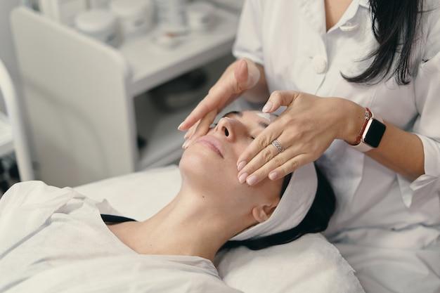 Молодая женщина лежит с закрытыми глазами, косметолог делает процедуру Бесплатные Фотографии