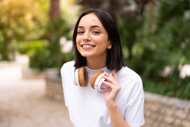 屋外で音楽を聴く若い女性 Premium写真