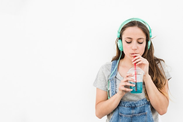 Young woman listening music on headphone drinking juice Free Photo