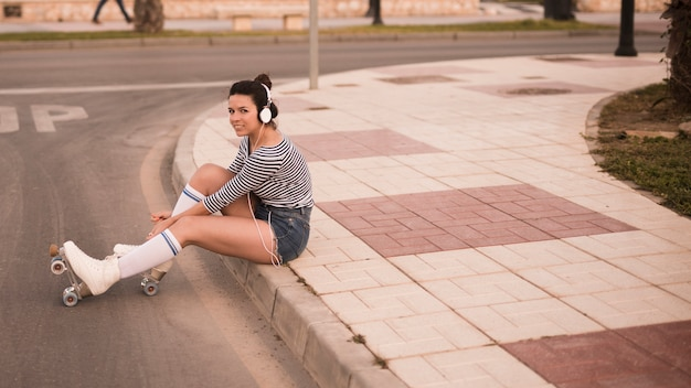 Young woman listening music on headphone relaxing on road Free Photo