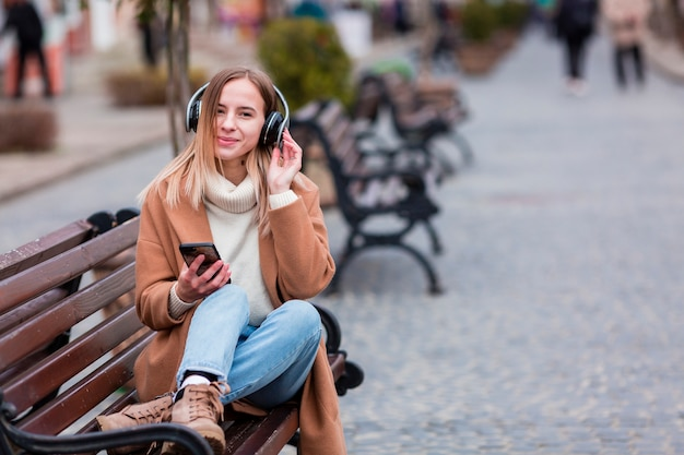 Young woman listening to music on headphones with copy space Free Photo