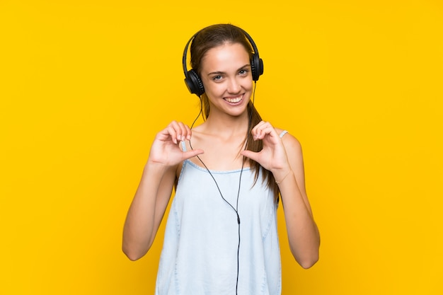 Young woman listening music over isolated yellow wall proud and self-satisfied Premium Photo