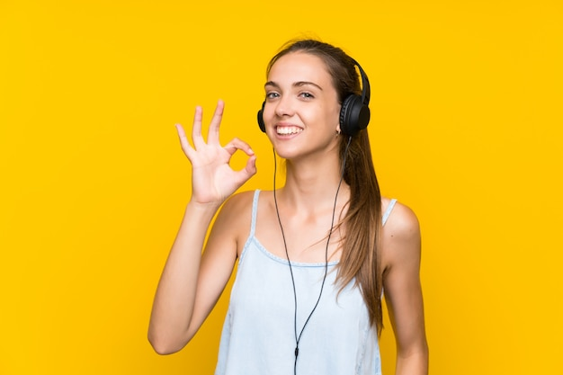 Young woman listening music over isolated yellow wall showing ok sign with fingers Premium Photo