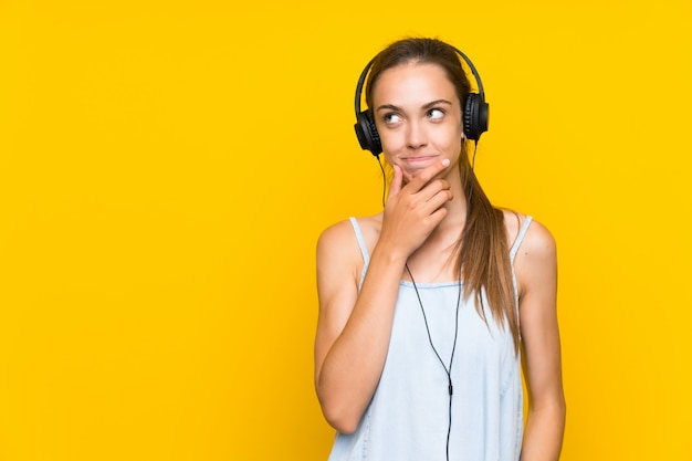 Young woman listening music over isolated yellow wall thinking an idea Premium Photo