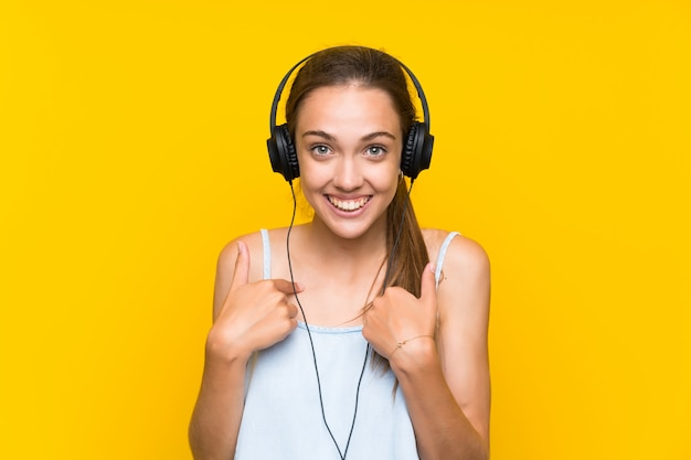 Young woman listening music over isolated yellow wall with surprise facial expression Premium Photo