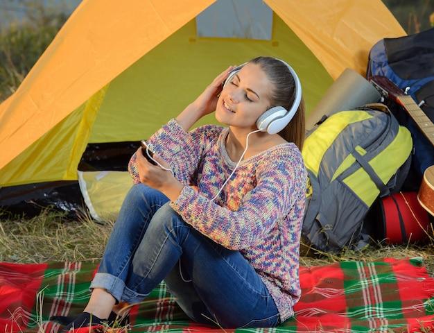テントの中でmp3プレーヤーを聴く若い女性 Premium写真