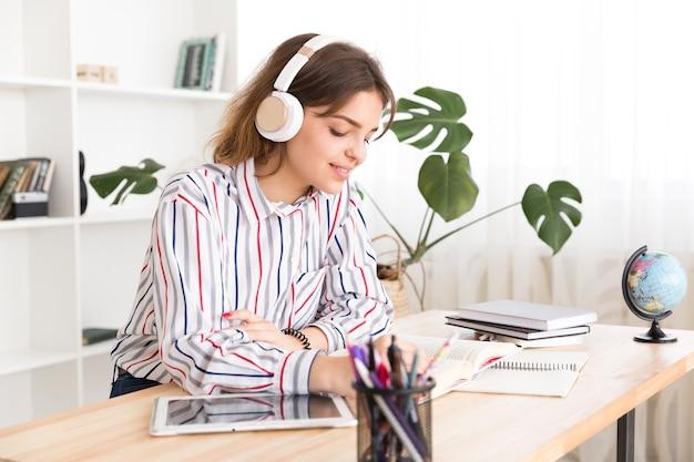 Молодая женщина слушает музыку и читает Premium Фотографии