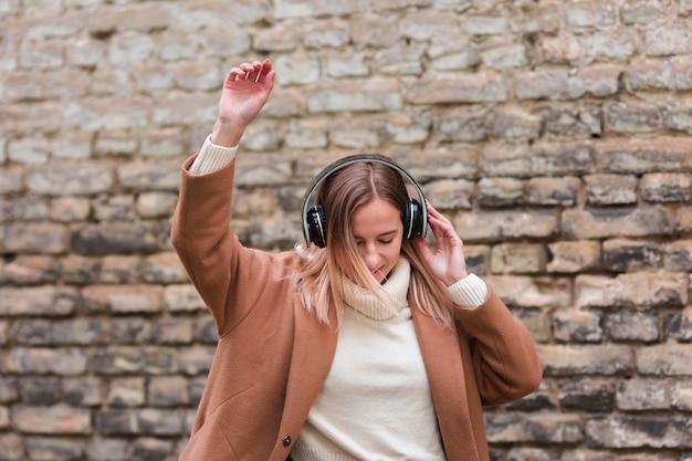 外のヘッドフォンで音楽を聴く若い女性 無料写真