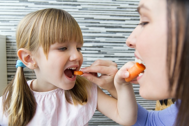 Young woman and little girl eating carrots in the kitchen Free Photo