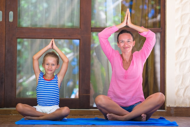 Young woman and little girl engaged in fitness outdoor on terrace Premium Photo